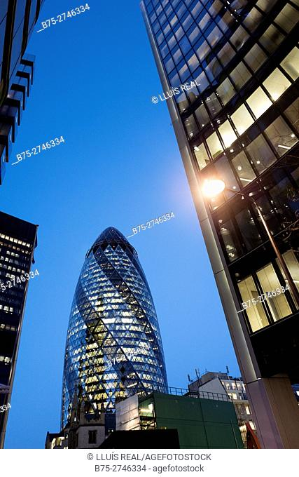 Sunset view of modern architecture building, 30 St Mary Axe, widely known informally as The Gherkin, with a lamppost in the foreground