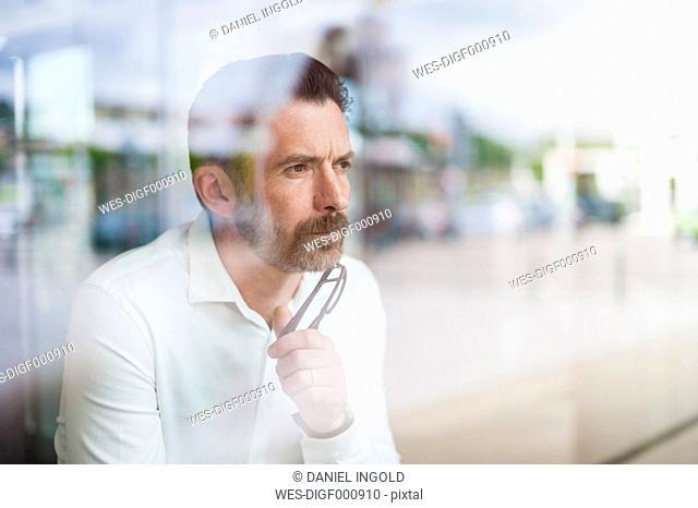 Portrait of serious businessman looking through window