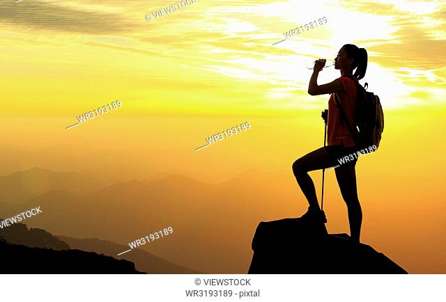 Young woman standing in the top of the mountain