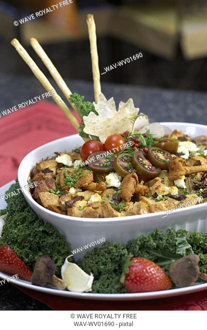Egg soufflé with wild mushrooms and goat cheese garnished with black cherry tomatoes, breadsticks, kale and strawberries