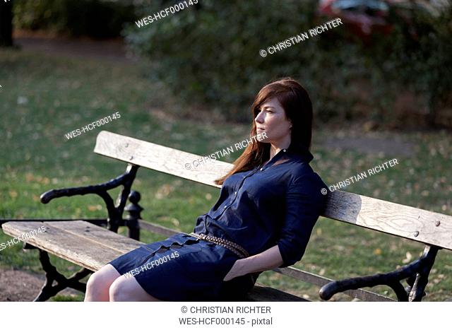 Portrait of woman sitting on a park bench