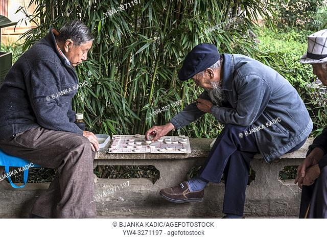 Locals playing Go - Chinese board game, Green Lake Park, or Cuihu Park, a local central located park, Kunming, Yunnan province, China