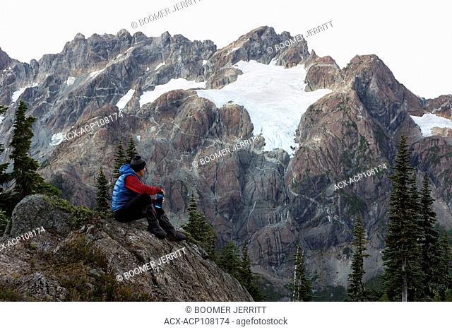 A lone hiker looks up to the Septimus/Rousseau massif and it's hanging glacier while camping overnight on the Flower Ridge trail, Strathcona Park
