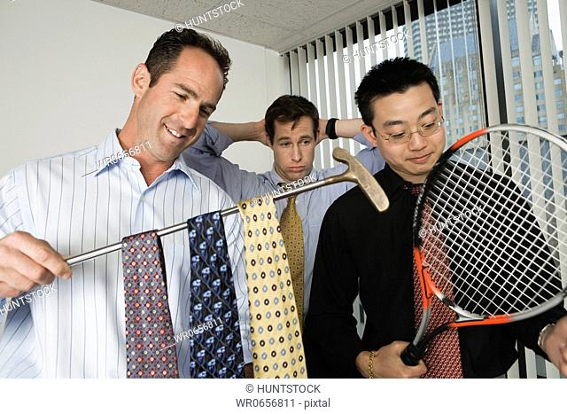 View of businessmen holding a golf club and a tennis racket