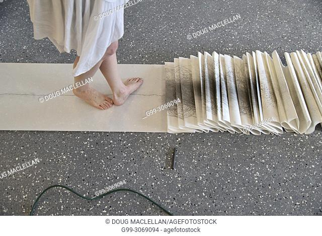 A side view from the knees down of a woman artist in a white dress turning as she creates a performance art work at an artist run gallery in Windsor, Canada