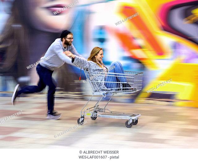 Young man pushing woman in shopping cart, laughing and running