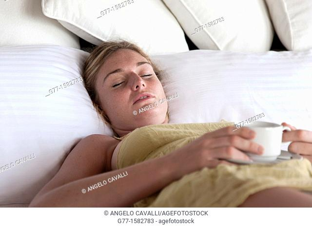 Maldives Islands Ari Atoll Woman in bed with a cup of coffee