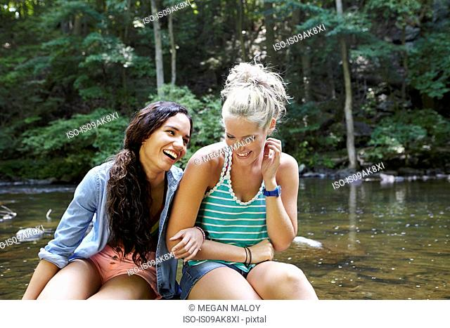 Women sitting by river in forest