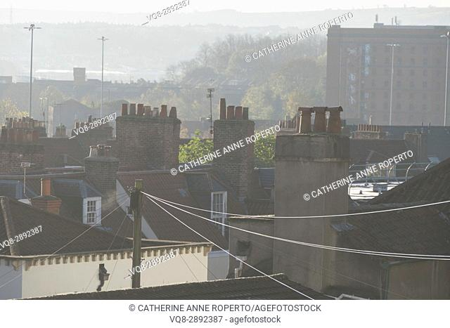 Early morning summer haze over C18th rooftops and chimney pots with tobacco factory backdrop, Hotwells, Bristol, England, UK