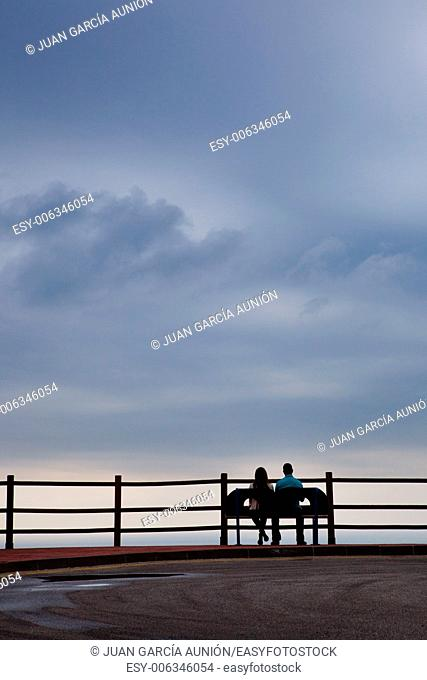 Silhouette of a heterosexual young couple on a calm and peaceful cloudy day, relaxing in front of the ocean view