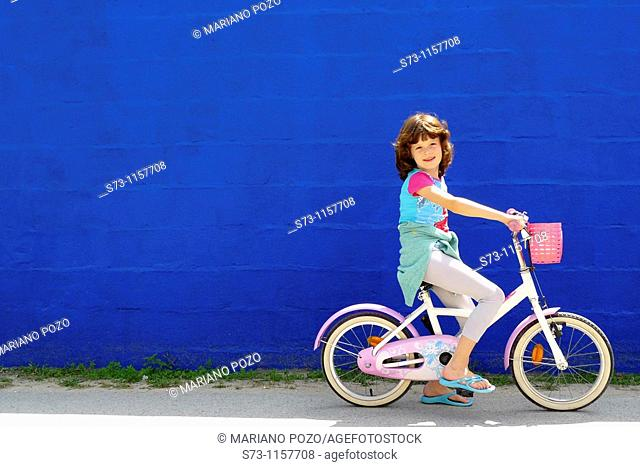 7 years old girl on bicycle front a blue wall in Caños de Meca, Cádiz, Andalucia, Spain