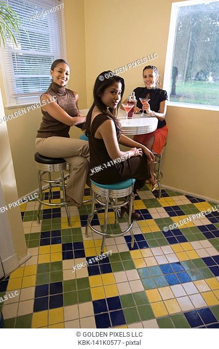 Three women having drinks in kitchen