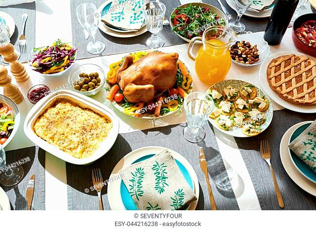 Top view of festive dinner table with delicious turkey and homemade dishes on it, served with robin blue plates and napkins in sunlight , copy space background