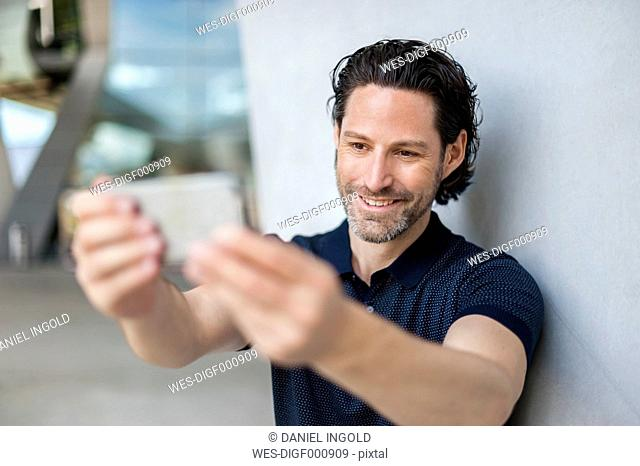 Portrait of smiling man taking selfie with cell phone