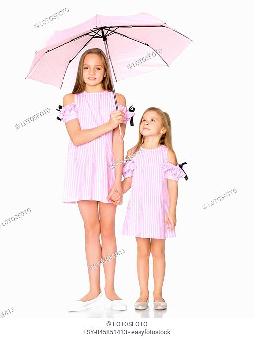 Lovely little girls hid under the umbrella. The concept of a happy childhood, family vacation. Isolated on white background