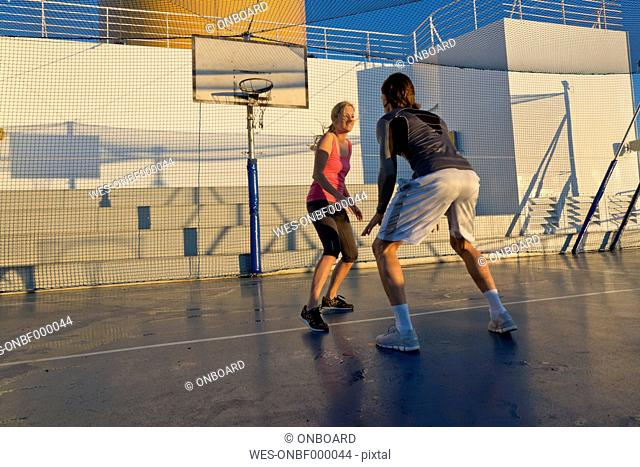 Couple playing basketball on a deck of a cruise ship