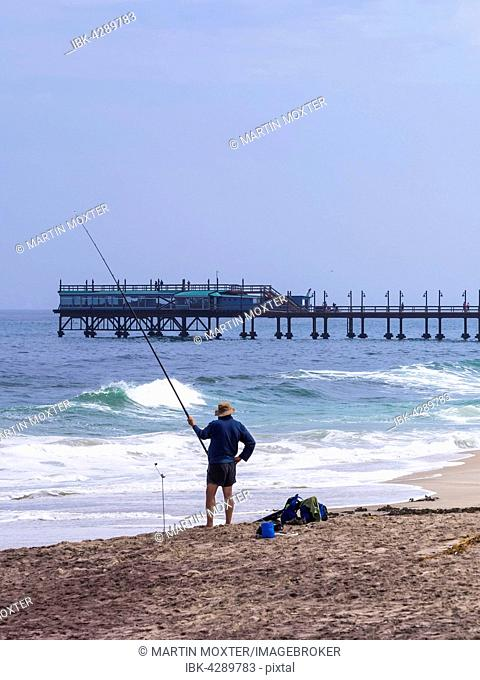 Angler standing on the beach fishing, in the back an old jetty, Swakopmund, Namibia
