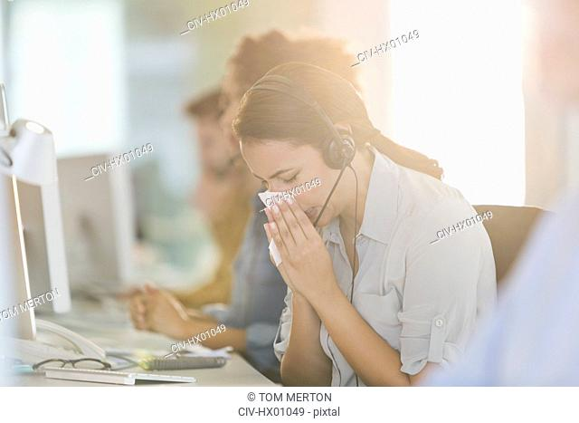 Businesswoman with headset blowing nose at computer in work