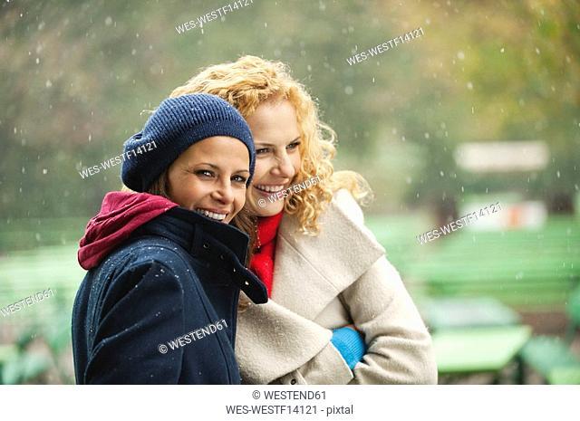 Germany, Bavaria, English Garden, Two women in beer garden, laughing, portrait