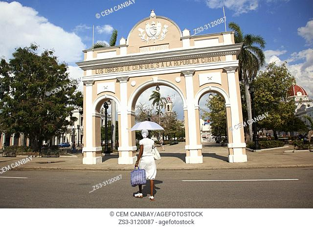 Cuban woman wearing white dress in front of the Arch Of Triumph-Arco Del Triunfo at Parque Jose Marti in Plaza de Armas Square, Cienfuegos, Cuba, West Indies