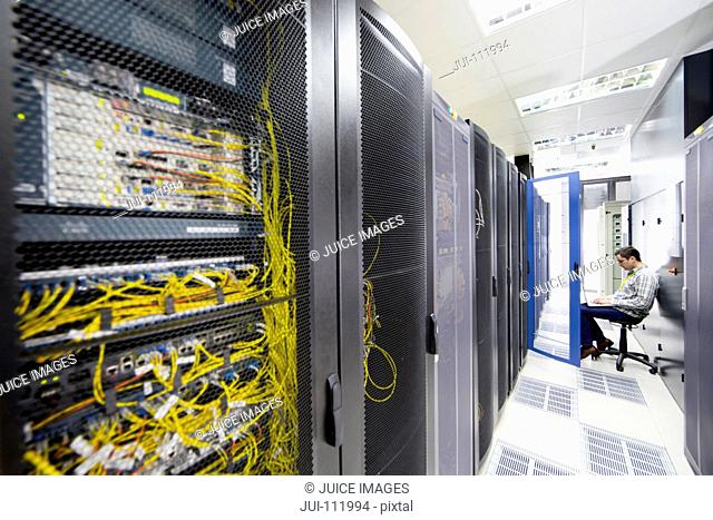 Technician with laptop checking server in data centre hall