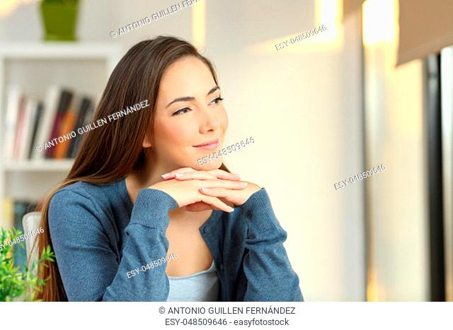 Confident pensive woman looking at side in a room at home