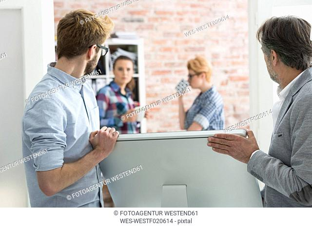 Two men carrying computer screen in office
