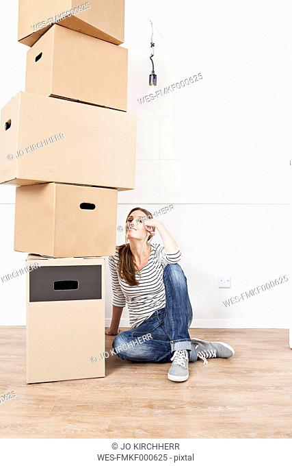 Woman sitting on floor besides stack of cardboard boxes