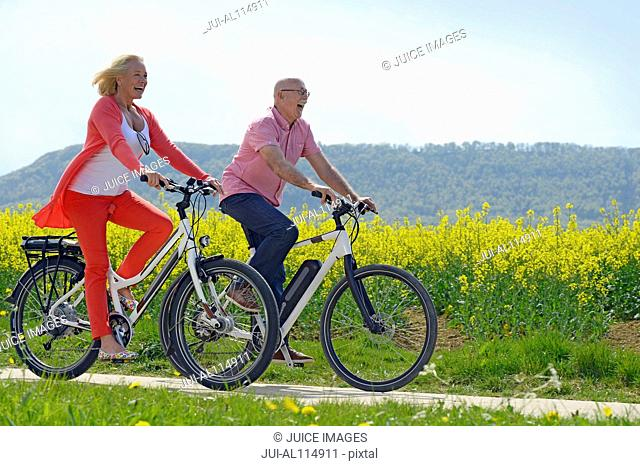 Older couple riding bicycle next to field