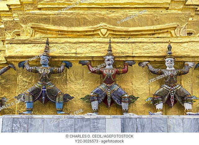 Bangkok, Thailand. Yakshas (Demons) Supporting the Gilded Chedi, Royal Grand Palace Compound