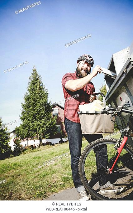 Portrait of laughing cyclist recycling waste paper in paper bank