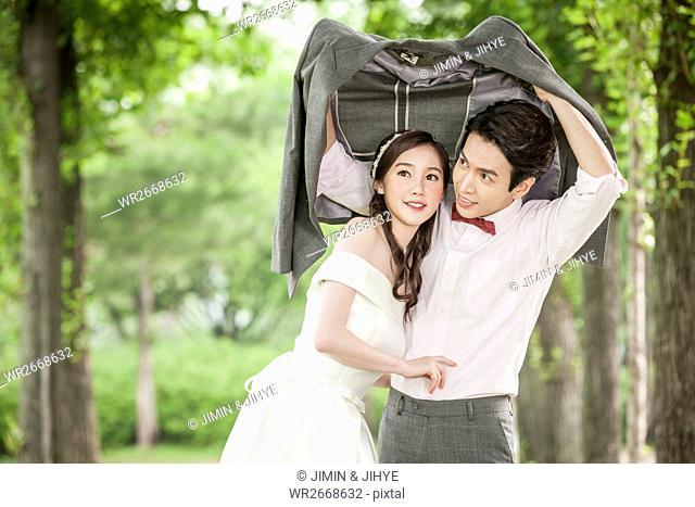 Young romantic wedding couple posing outdoors