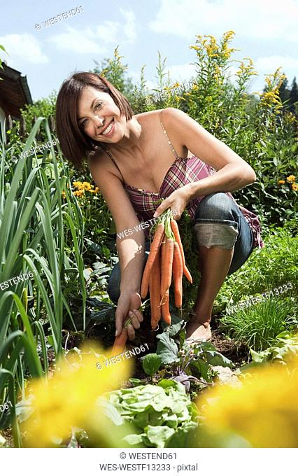 Germany, Bavaria, Woman holding bunch of carrots in garden, smiling, portrait