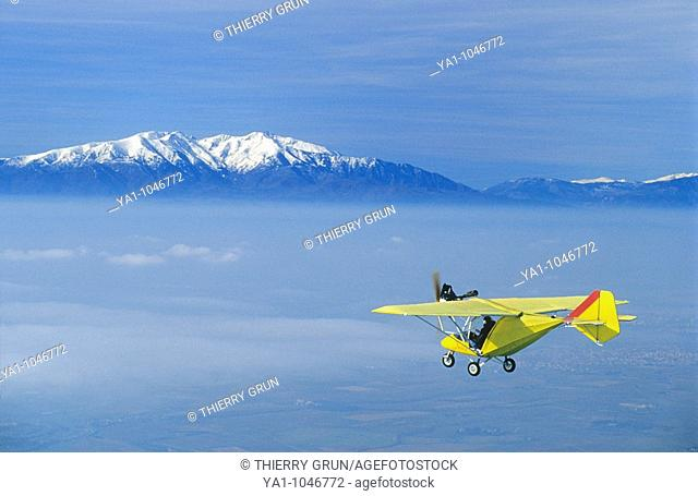 Ultra light plane flying in wintertime over thin clouds arround Torreilles. At background the snowed Canigou peak (2784 m)