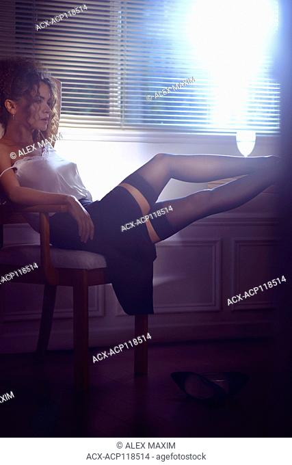 Sensual boudoir portrait of a young woman sitting in a chair by the window half undressed with her legs in sexy stockings on a table
