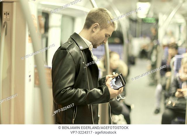 man in public transport, phone, earphone, headphone