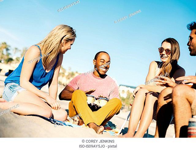 Man with friends bongo drumming on beach, Santa Monica, California, USA