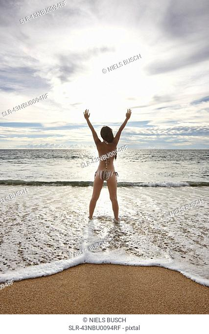 Woman standing in surf on beach