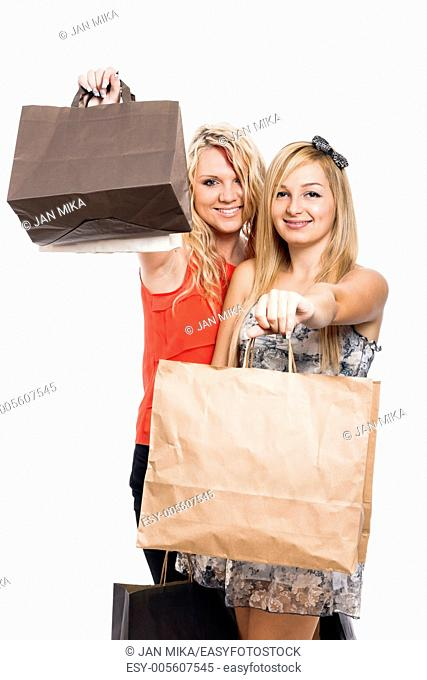 Two happy girls holding shopping bags, isolated on white background