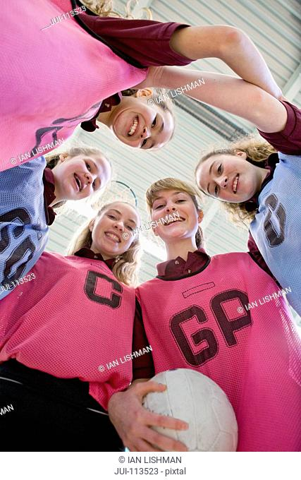 Portrait smiling high school students in huddle with netball