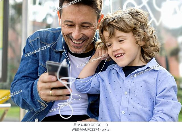 Happy father and son sharing cell phone and earbuds