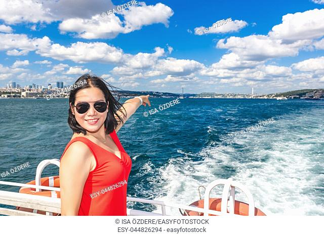 Beautiful Chinese woman shows First Bridge while cruising with ferry in Istanbul,Turkey