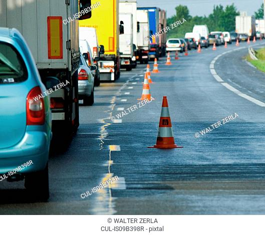 Rear view of rows of traffic queueing on highway with traffic cones