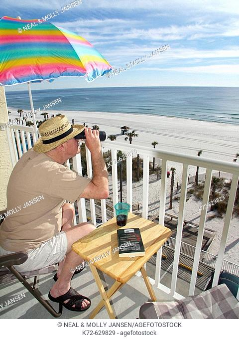 Elderly man looking through binoculars from his balcony