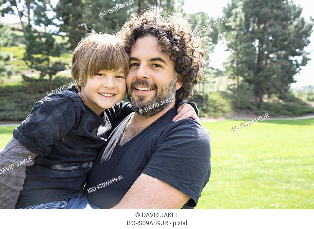 Portrait of proud father and son in park