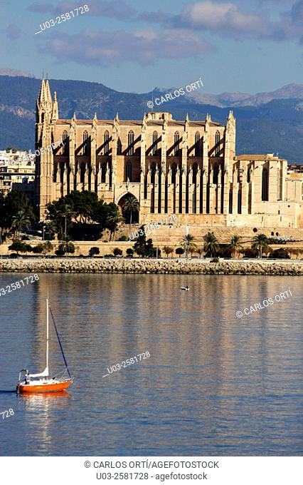 Boat sailing in front of the Cathedral of Palma de Mallorca, Spain