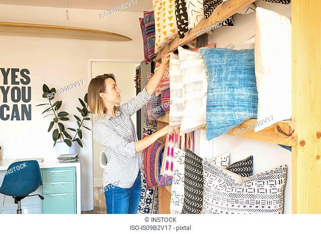 Female interior designer adjusting cushions on shelves in retail studio