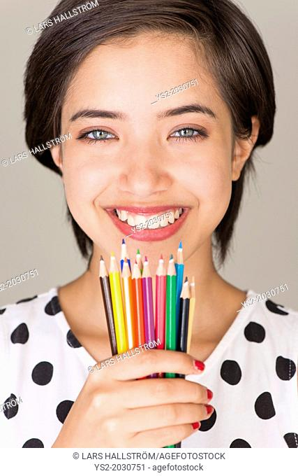 Beautiful young multiracial woman smiling and showing a set of colored pencils.1015