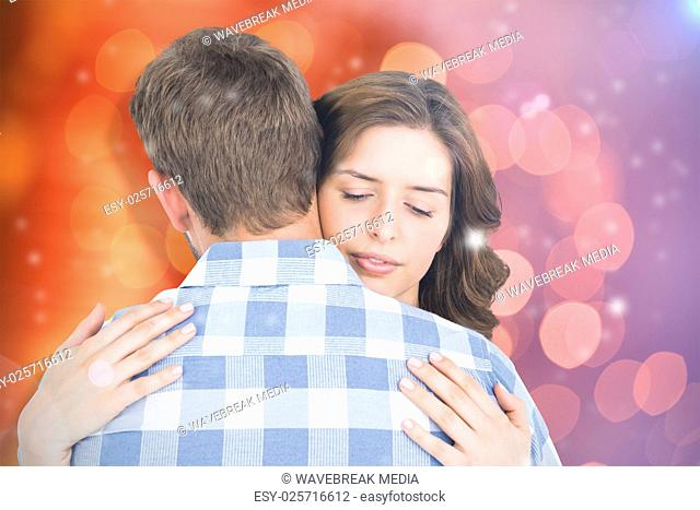 Composite image of happy young couple cuddling each other