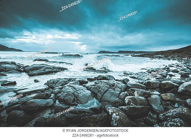 Dark storm clouds and huge waves batter a rock covered seashore in blue tones of suspense. Cloudy Bay, Bruny Island, Tasmania, Australia
